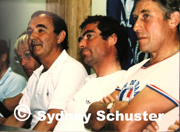 Many-times Tour de France winners Laurent Fignon, Bernard Hinault, and Jacques Anquetil (and some guy) at a Colorado Springs press conference, wishing they were someplace else.